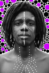 Portrait of young african man with dreadlocks and traditional face paint looking straight into the camera