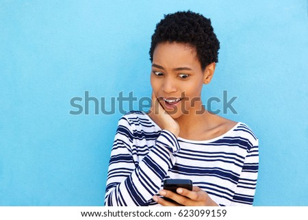 Portrait of young african woman looking confused at cell phone #623099159