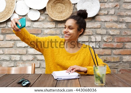 Portrait of young african woman sitting at cafe and taking selfie with her mobile phone #443068036