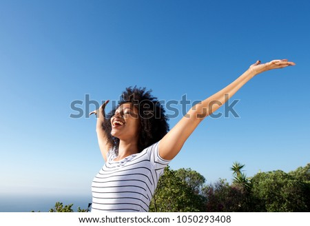 Portrait of young african woman standing outdoors with arms raised and laughing #1050293408