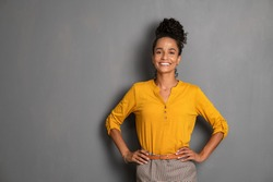 Portrait of young african woman standing with hands on waist and looking at camera. Confident stylish latin girl smiling isolated against grey background. Beautiful woman with copy space on gray wall.