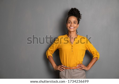 Portrait of young african woman standing with hands on waist and looking at camera. Confident stylish latin girl smiling isolated against grey background. Beautiful woman with copy space on gray wall. Foto stock ©