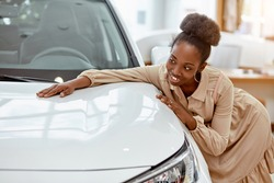 portrait of young africanamerican woman hugging new auto in cars showroom