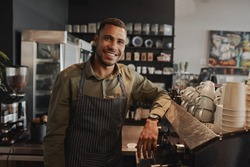 Portrait of young afro-american male business owner behind the counter of a coffee shop smiling looking at camera