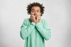 Portrait of young Afro American man with scared and anxious expression, bites finger nails, wears green sweater, being afraid of visiting doctor. Human facial expressions and negative emotions concept