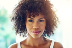 Portrait of young afro-american pretty girl looking at camera on blurred inside background.