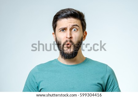 Portrait of young amazed man isolated on gray background