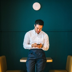 Portrait of young and attractive Chinese Asian business man using his smartphone and smiling. He is professionally dressed in a fitting shirt and pants in the office.