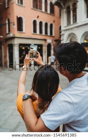 Portrait of young and beautiful Asian couple visit the city of Venice, Italy - Millennials on their honeymoon take a picture with a smart phone at buildings town square - The man embraces woman