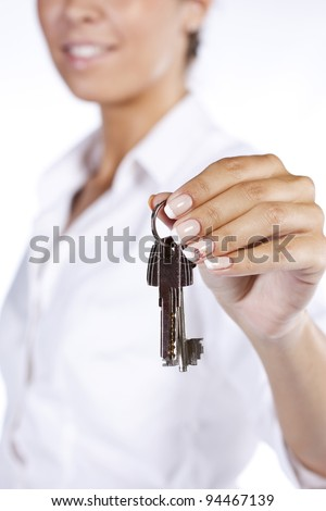Portrait of Young and beautiful business woman holding keys - Focus is on the keys