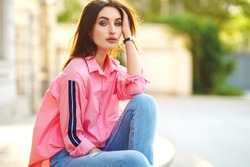 Portrait of Young and beautiful woman in casual clothes in the street. dressed in a pink shirt and jeans. spring / summer concept. relax time.  girl with blue eyes. Enjoy street sunset
