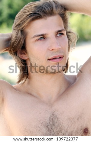 Portrait of young and handsome guy on the beach