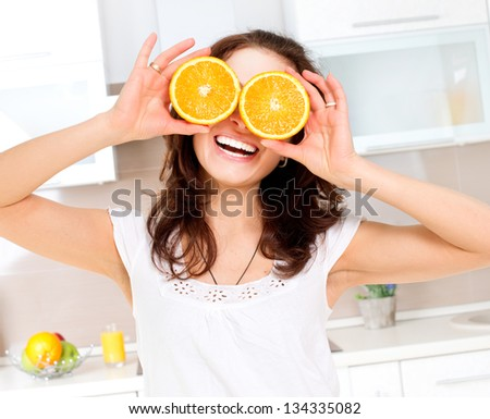 Portrait of Young and Healthy Funny Woman with Orange over Eyes in the Kitchen. Diet and Healthy Eating Concept