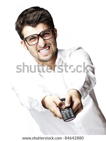 portrait of young angry man holding control tv over white background