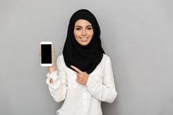 Portrait of young arab woman 20s in islamic headscarf with oriental makeup pointing finger on black screen of cell phone isolated over gray background