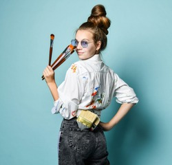 Portrait of young artist at work. Young woman in shirt with paint stains and rectangular sunglasses with a set of brushes is standing back, looking over her shoulder at us on gray