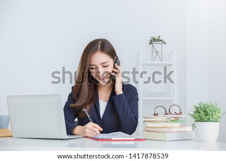 Portrait of young asian business woman talk on smartphone write in notebook with laptop in office. Beautiful girl desk with computer take order, Startup businesswoman online telemarketing sme concept