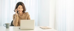 Portrait of young asian business woman talk on smartphone write notebook laptop in home office. Beauty girl at desk computer take order. Startup business asia woman online telemarketing sme banner