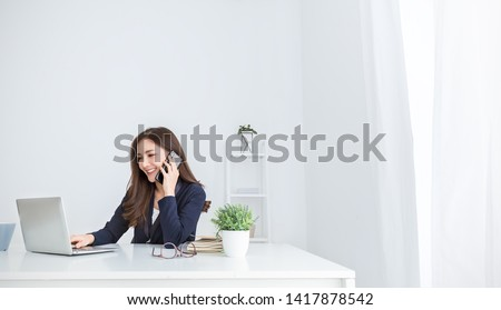 Portrait of young asian business woman talk on smartphone write notebook laptop in home office. Beautiful girl at desk computer take home order. Startup business asia woman online sme telemarketing.