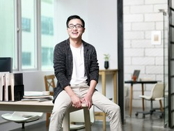portrait of young asian businessman sitting on desk in office looking at camera laughing
