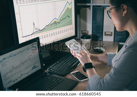portrait of young asian businesswoman using calculator to count new exchange rate. seriously girl focus on trading currency.