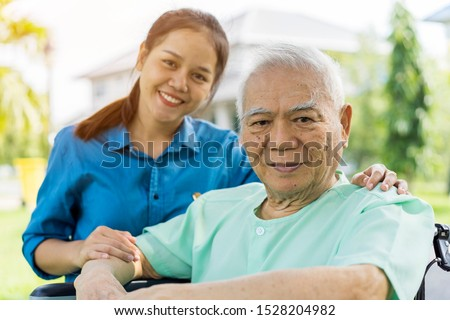 Portrait of Young Asian caregiver in uniform hugging smiling elderly man or patient in wheelchair during a home visit and spending time together. Love, Family or Assistant or elderly caregiver concept