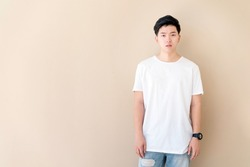 portrait of Young Asian casual teenage boy indicate blank space on Beige background.