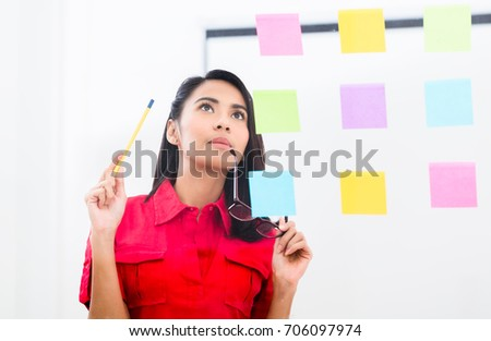 Portrait of young Asian employee looking at multiple reminders while planning her work in the office