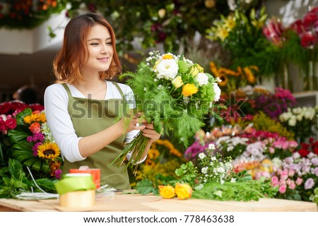 Portrait of young Asian florist wearing apron standing at counter and focused on making bouquet for client, interior of flower shop on background Photo stock ©