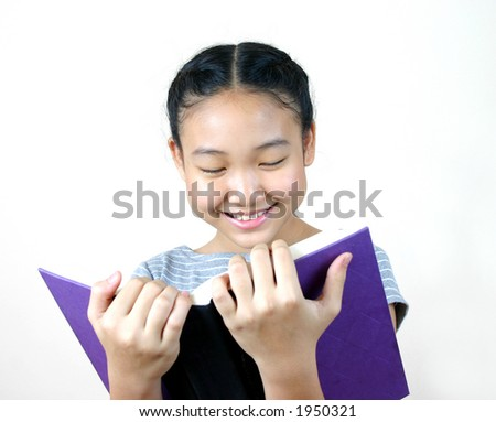 Portrait of young asian girl reading a book.