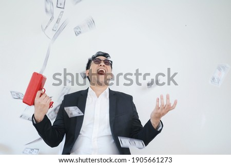 Portrait of young Asian man looking money falling in the air, lucky man with his money. Stock photo ©