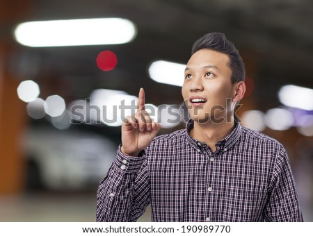 portrait of young asian man pointing up with finger