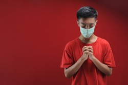 Portrait of  young Asian man wearing protective mask against the coronavirus, doing pray for corona virus is quickly overcome isolated on red color