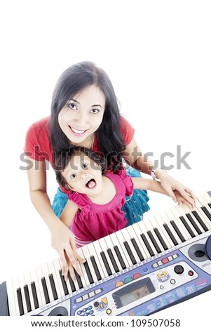 Portrait of young asian mother and her daughter playing piano. isolated on white