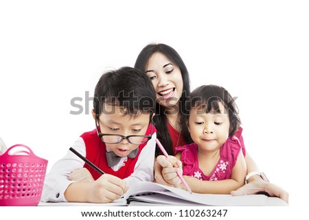 Portrait of young asian mother guiding her children to draw on the paper