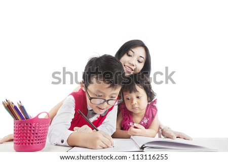 Portrait of young asian mother guiding her children to study at home