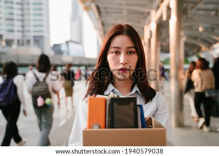 Portrait of young Asian woman holding box of items after being laid off from job due to recession and economic stress in industry Stockfoto ©