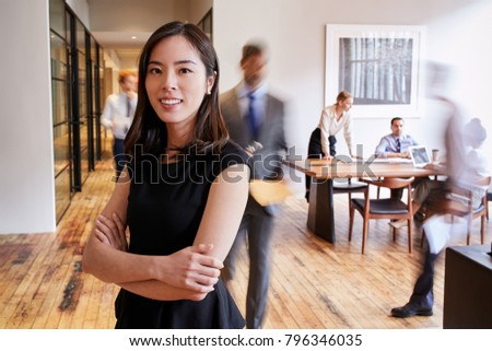 Portrait of young Asian woman in a busy modern workplace