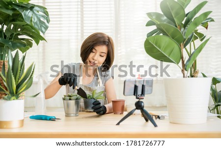 Portrait of young asian woman planting plant pot to fan channel, record home video. Online influencer girl in social media marketing live her hobby, lockdown coronavirus new normal sme small business Сток-фото ©