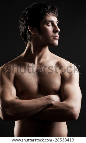 portrait of young athletic man against dark background