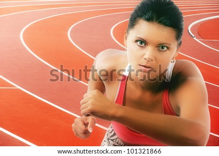 Portrait of young athletic woman running on track