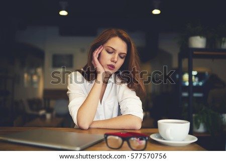 Portrait of young attractive administrative manager resting in coffee shop during work break thinking over financial report made on laptop computer  while waiting for informal meeting with owner