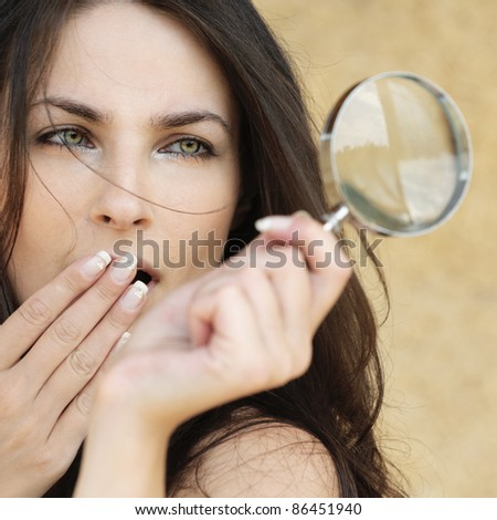 Portrait of young attractive amazed woman holding loupe and covering her mouth with hand against yellow background.