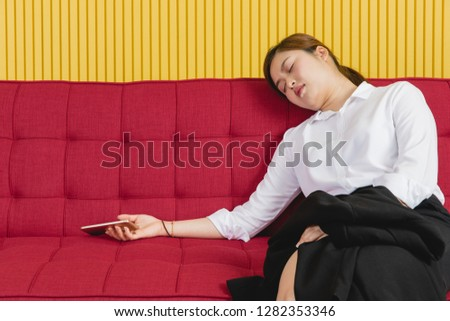 Portrait of young attractive Asian businesswoman, exhausted, fatigue from overworked on long and busy working days, doze off, fell asleep on big red sofa in modern office, smartphone still in hand