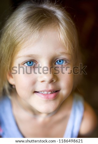 Portrait of young attractive beautiful blonde girl with blue eyes with a smiling and positive expression of the face #1186498621