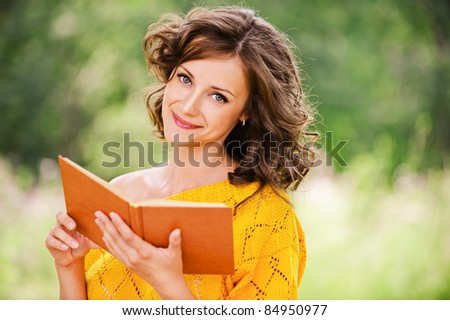 Portrait of young attractive beautiful dark-haired curly woman wearing orange sweater and holding book at summer green park.