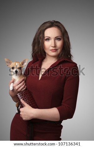 Portrait of young attractive brunette woman holding little Chihuahua dog on her hands