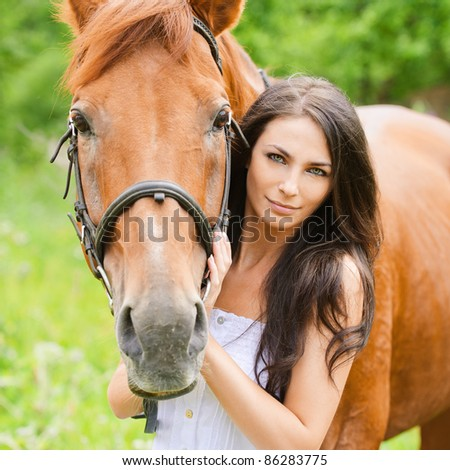 Portrait of young attractive brunette woman wearing white dress with horse at summer green park.