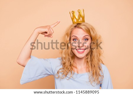 Portrait of young attractive charming nice cute caucasian curly-haired blonde girl wearing golden crown and blue dress, pointing to diadem, toothy smile. Isolated over beige background