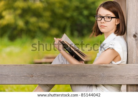Portrait of young attractive earnest brunette woman wearing white clothes, reading book, sitting at summer green park.